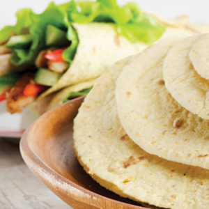 Stack of Tortillas with Burrito in Background