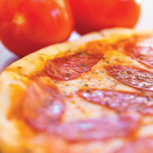 Close up of Pepperoni Pizza with Tomatoes in background