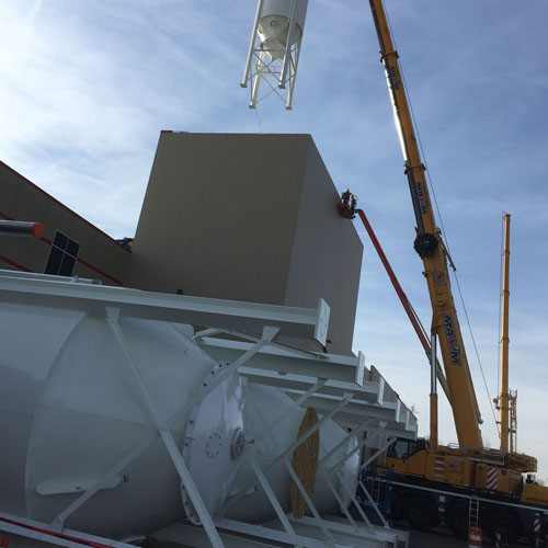 Close up of Crane Raising Storage Silo onto Building