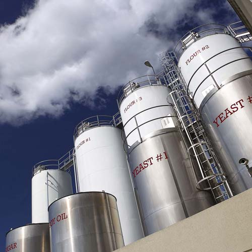 Eight Labeled Outdoor SIlos, Including Sugar, Yeast, Soy Oil, and Flour